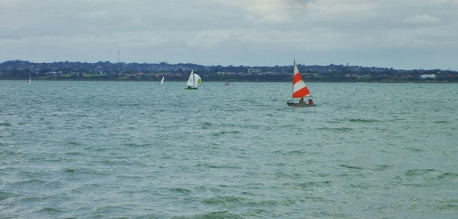 Love the red and white sail on the small yacht.